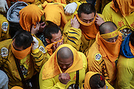 Men cover their faces with towels moments before a large pile of firecrackers are lit at their feet.