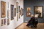 Ann Bates O.B.E.(in wheelchair) in front of Anne (R) by Paul Brason - The Royal Society of Portrait Painters Annual Exhibition at the Mall Galleries. It includes over 200 portraits by over 100 artists.