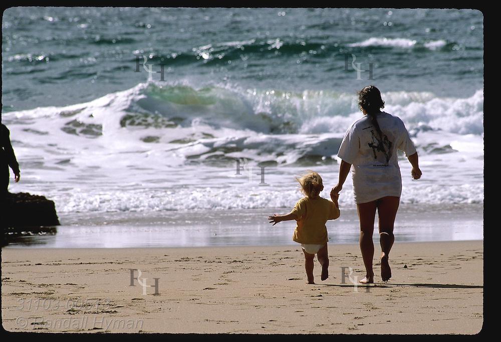 Mom & diaper girl run toward the chilly North Atlantic surf of Coumeenole Beach;  Dunmore Head, Dingle Peninsula, Ireland.