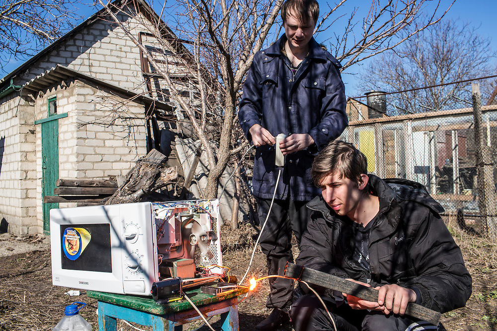 LUHANSK, UKRAINE - MARCH 16, 2015: Aleksandr Kryukov, left, and Pavel Pavlov use a microwave to creat electrical sparks in the yard of the house where Kryukov lives with his grandmother in Luhansk, Ukraine. The two have created a series of popular YouTube videos involving scientific experiements. CREDIT: Brendan Hoffman for The New York Times