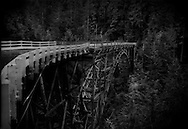A one-lane logging-road bridge over a deep and narrow gorge up the Carbon River near the base of Mt. Rainier.  Washington State, USA.  This aging bridge is high enough to be unaffected by all but the worst lahar mudflows if the volcano erupts.