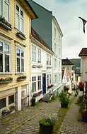 Timber houses decorated with colourful window boxes on a cobbletstone street in the Nordness section of Bergen, Norway, Europe