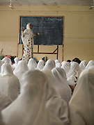 Teacher training in a classroom in Zanzibar, Tanzania. The students are sitting on the floor with one teacher at the front with a black board.