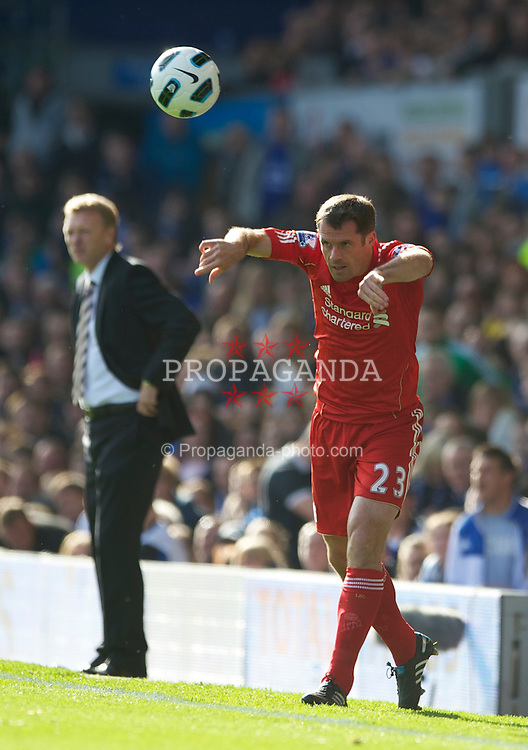 LIVERPOOL, ENGLAND - Sunday, October 17, 2010: Liverpool's Jamie Carragher takes a throw-in as Everton's manager David Moyes looks on during the 214th Merseyside Derby match at Goodison Park. (Photo by David Rawcliffe/Propaganda)