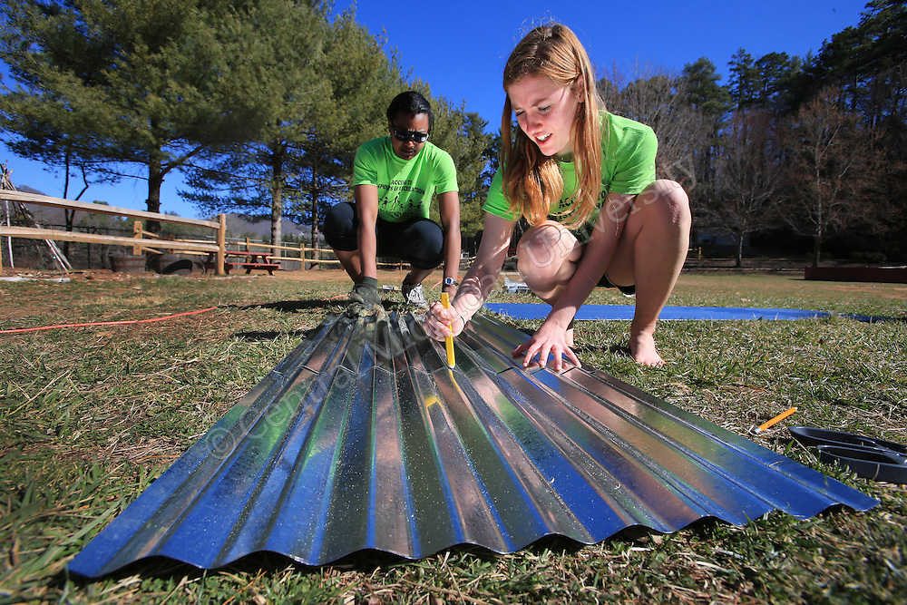 Alexandria Roberts, of Canton, (left) and Nicole Rombach, of Davisburg, (Right) cut metal for a roof of a garden kiosk they were helping build. They were among nine CMU students spending their Alternative Break volunteering at  theYMCA of Western NC Youth Service Center, spending the week to help with projects to improve the center and in the community. They addressed access to sports and recreation and built a kiosk, cleared a stream bed and worked with elementary students in an after school program as their Alternative Break project. CMU is ranked fourth in the nation for the number of students participating in Alternative Breaks and fifth in the country for the most trips coordinated by a university. The program organizes about 40 trips each year with more than 400 students participating. Photo by Steve Jessmore/Central Michigan University