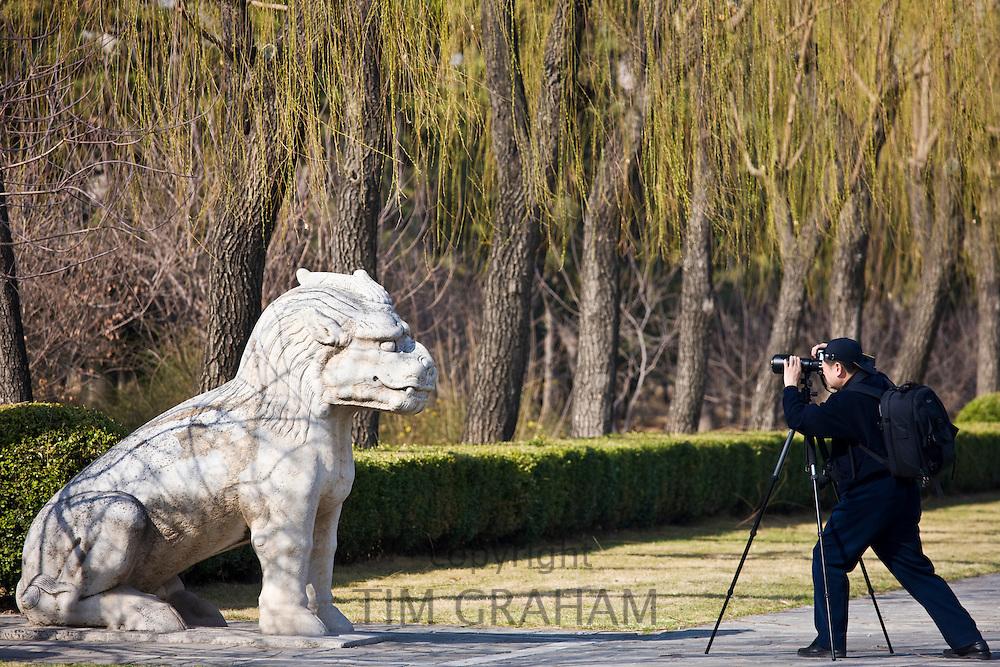 Man photographs statue of a resting Xiezi, a mythical Chinese Unicorn, Spirit Way, Ming Tombs, Beijing, China