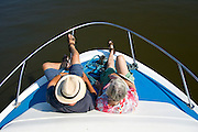 Passengers sit at the bow of a river cruiser on the Broadlands, Norfolk, United Kingdom