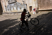 A cyclist pushes his bike up a steps as another man bends in the hot sun.