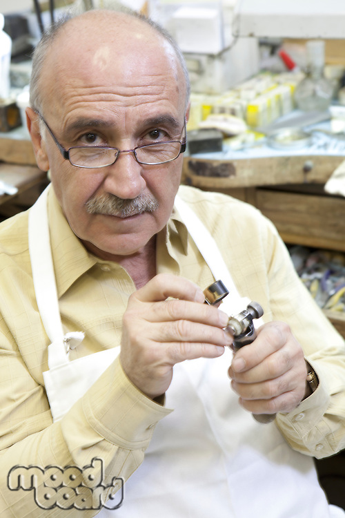 Portrait of a mature repair worker with loupe in workshop