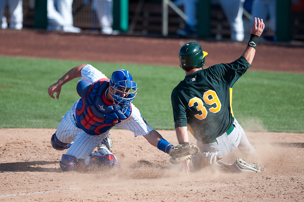MESA AZ - MARCH 4: Jason Pridie #39 of the Oakland Athletics gets tagged out by Micah Gibbs of the Chicago Cubs at home plate during a spring training game at HoHoKam Stadium on March 4, 2012 in Mesa, Arizona. (Photo by Rob Tringali) *** Local Caption *** Jason Pridie;Micah Gibbs