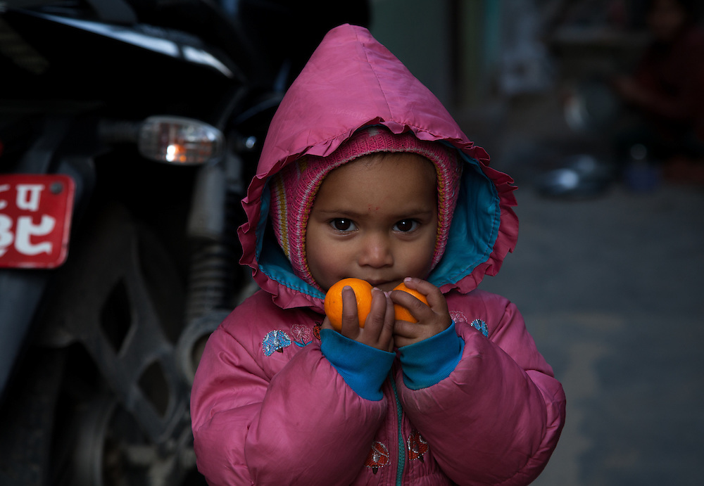 A young girl poses with two pieces of fruit.