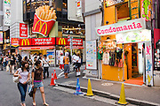 Two girls walk past a Condomania condom shop and a McDonald's fast food outlet in Shibuya District, Tokyo, Japan.