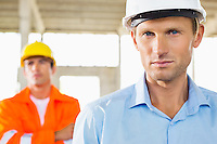 Portrait of confident architect at construction site with coworker in background