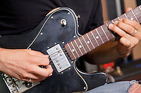 Close-up view of man playing electric guitar