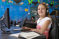 School girl wearing headphones in computer room, portrait