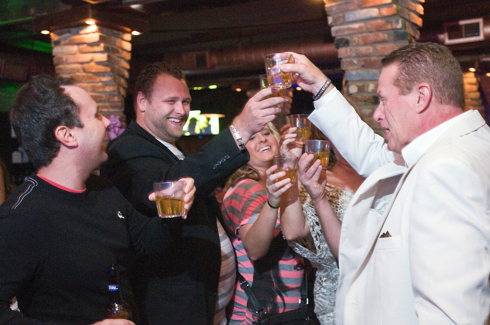 Brandon Paquin, left, and Jamason Welker and his wife Amanda, center, raise their glasses for a toast with Doc Smith, right, and his wife Cathy Lynn, at Baxter's 942 Bar and Grill on Baxter Avenue Saturday, Aug. 11, 2012 in Louisville, Ky. Jamason bought the round for his friends for supporting him in his efforts to promote music. (Photo by Brian Bohannon)