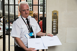 London, UK. 17 July, 2019. A security guard at the headquarters of the Conservative Party accepts letters from campaigners from Age UK and Lewisham Pensioners Forum who had collected more than 30,000 letters calling on the Government to reverse the axing of free TV licences for over-75s. Credit: Mark Kerrison/Alamy Live News