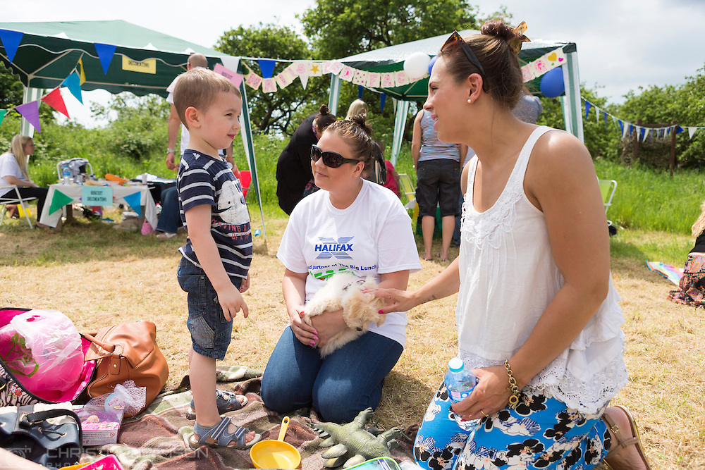 20140601 Free for editorial use image<br /> <br /> Halifax colleagues in Bournemouth are proud to give extra back to their local community by hosting their Big Lunch event on Sunday 01 June 2014.<br /> <br /> Halifax staff member Stacie Dicker (centre) chats with Joshua during The Big Lunch at the New Leaf Allotment in Bournemouth. <br /> <br /> For more information please contact: Catherine Eastham on 020 3697 4304<br /> <br /> If you require a higher resolution image or you have any other onEdition photographic enquiries, please contact onEdition on 0845 900 2 900 or email info@onEdition.com<br /> This image is copyright the onEdition 2014&copy;.<br /> This image has been supplied by onEdition and must be credited onEdition. The author is asserting his full Moral rights in relation to the publication of this image. Rights for onward transmission of any image or file is not granted or implied. Changing or deleting Copyright information is illegal as specified in the Copyright, Design and Patents Act 1988. If you are in any way unsure of your right to publish this image please contact onEdition on 0845 900 2 900 or email info@onEdition.com