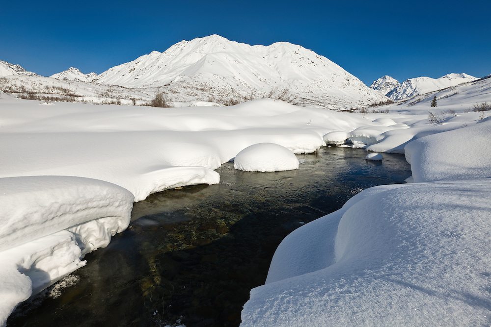 Deep snow lines the banks of the Little Susitna River with Idaho Peak and the Talkeetna Mountains in the background in Hatcher Pass in Southcentral Alaska. Afternoon. Winter.