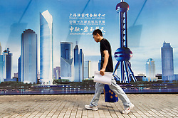 Man walks past billboard advertising modern property development in Pudong financial district of Shanghai