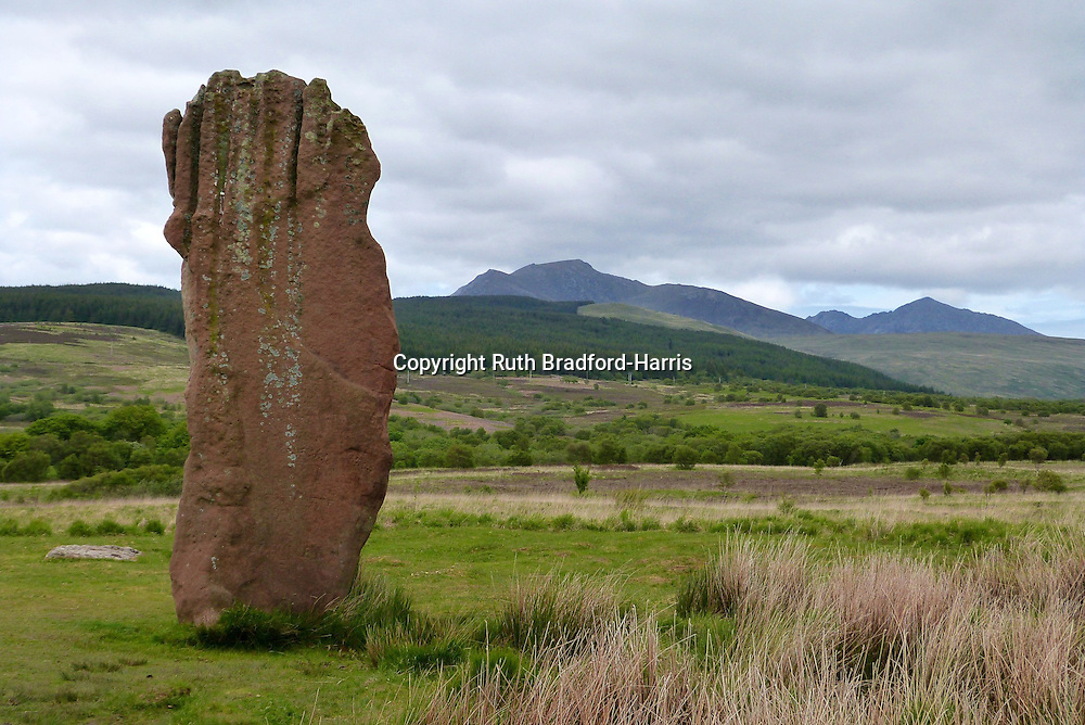 An unusual Old Red Sandstone Neolithic standing stone on Machrie Moor, Isle of Arran, with the mountain peaks of Beinn Nuis, Beinn Tarsuinn, North Goat Fell and Goat Fell beyond under a stormy sky.<br />