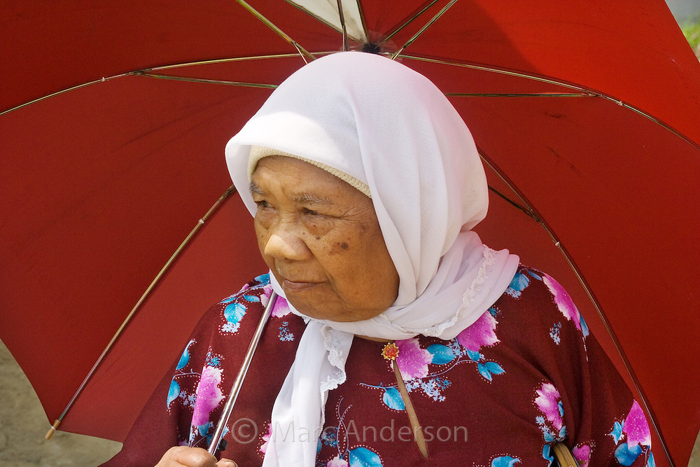 An old Malaysian woman wearing a white headscarf and holding a red umbrella..