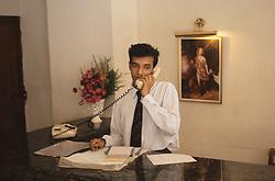 Receptionist working behind desk at the Sangheeta Hotel; Cochin; Kerala; India; talking on telephone,