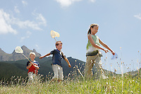Three children (7-9) walking through field holding butterfly nets low angle view.