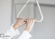 Haende einer Seniorin am Haltegriff eines Krankenbettes (model-released)
