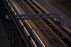 Stock photo of chemical plant pipes reflecting the setting sun