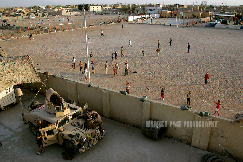IRAQ, BASRA - JULY 4: Iraqi children play soccer next to a US Marine Corps Military Training Team (MiTT) base in the poverty stricken neighbourhood of Hayaniyah, July 4, 2008 in Basra, Iraq. When British forces withdrew in 2007, Basra deteriorated into street battles between numerous Shiite militias and criminal gangs. In April 2008, Iraqi prime minister, Nouri al Maliki, sent two Iraqi army divisions to retake control of Basra. While the fighting has ended, unemployment is rife, at about 70 per cent. Since early 2008, Iraq's security situation has improved with oil production increasing, record government surplus and easing sectarian tensions. (Photo by Warrick Page)
