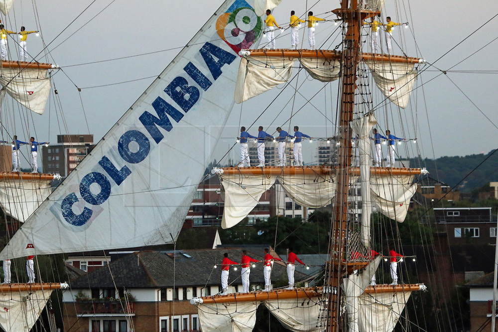 """© Licensed to London News Pictures. 06/09/2015.  The banks of the River Thames were packed with spectators to see the Colombian flagship ARC Gloria go through Tower Bridge to celebrate Colombia Day. The three masted sail training ship had 67 crew members balancing on the masts singing the Colombian national anthem as she sailed under Tower Bridge at 7pm and back under at 7.30pm as the sun set behind her. The ship has been in London for several days. Onlookers enjoyed the spectacle on an evening of warm late summer sunshine. The ship has a crew of 150, including 67 final-year cadets from the Colombian Naval Academy and one dog """"Black Pearl"""" the sailing black Labrador and the flagship's mascot. Credit : Rob Powell/LNP"""