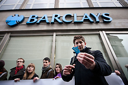 © licensed to London News Pictures. London, UK 10/02/2012. A protester cuts up his Barclays Bank debit card outside a branch of Barclays Banks in central London on February 10th, 2012, during a protest in support of the 'Move Your Money UK' campaign. Barclays today (10/02/2012) announces its annual results. Photo credit: Tolga Akmen/LNP