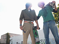 Two skateboarders laughing outdoors low angle view