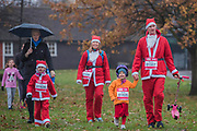 A family arrives - Participants of all ages don Santa suits for the London Santa Dash on Clapham Common. The event was to raise money for the Great Ormond Street Hospital (GOSH) Children's Charity and involved a 5 or 10k run.