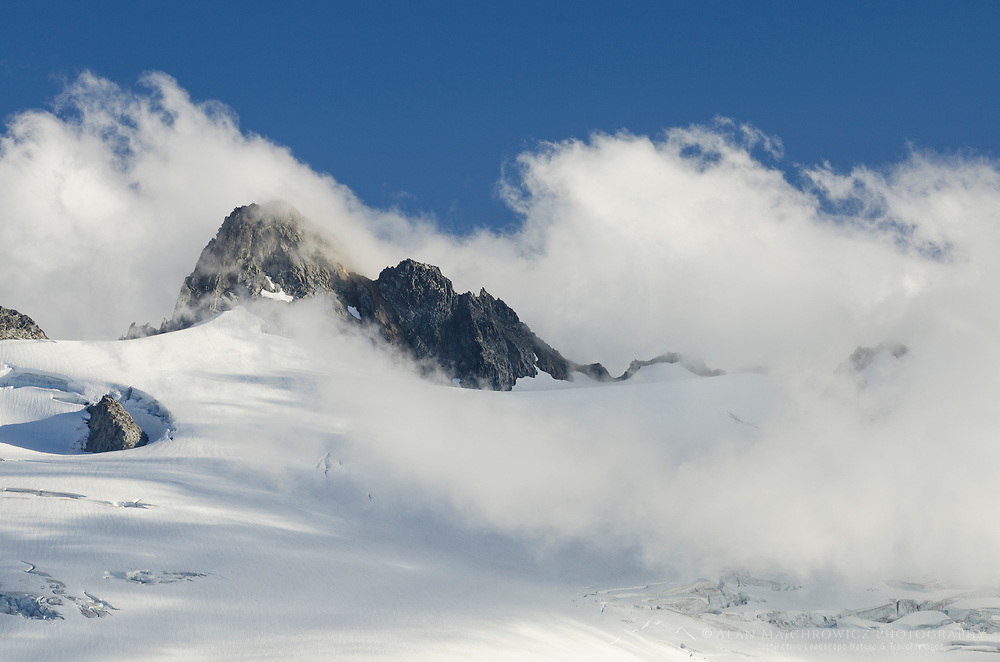 Clouds swirling around summit ridge of Mount Challenger, elevation: 8236 ft / 2510 m North Cascades National Park