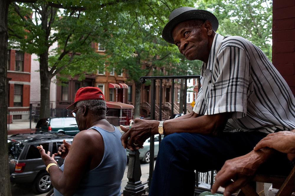 Russell Earl, left, and George Marvin, right, watch passersby from their stoop in Bed-Stuy beside the Nostrandt subway stop in Brooklyn, New York on June 24, 2012.
