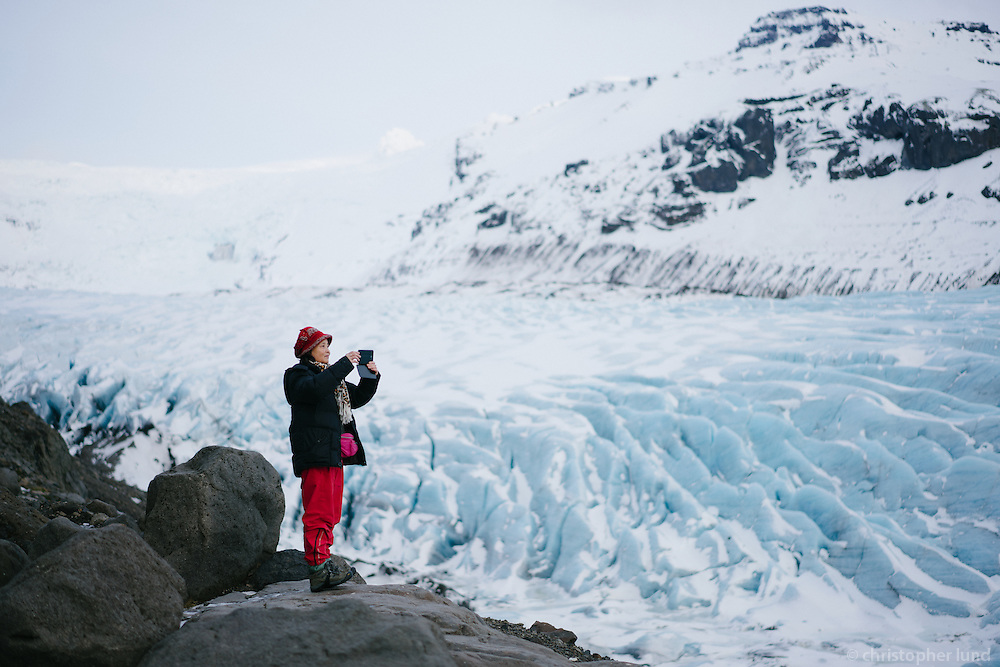 Asian tourist photographing the view at Svínafellsjökull outlet glacier, Southeast Iceland.