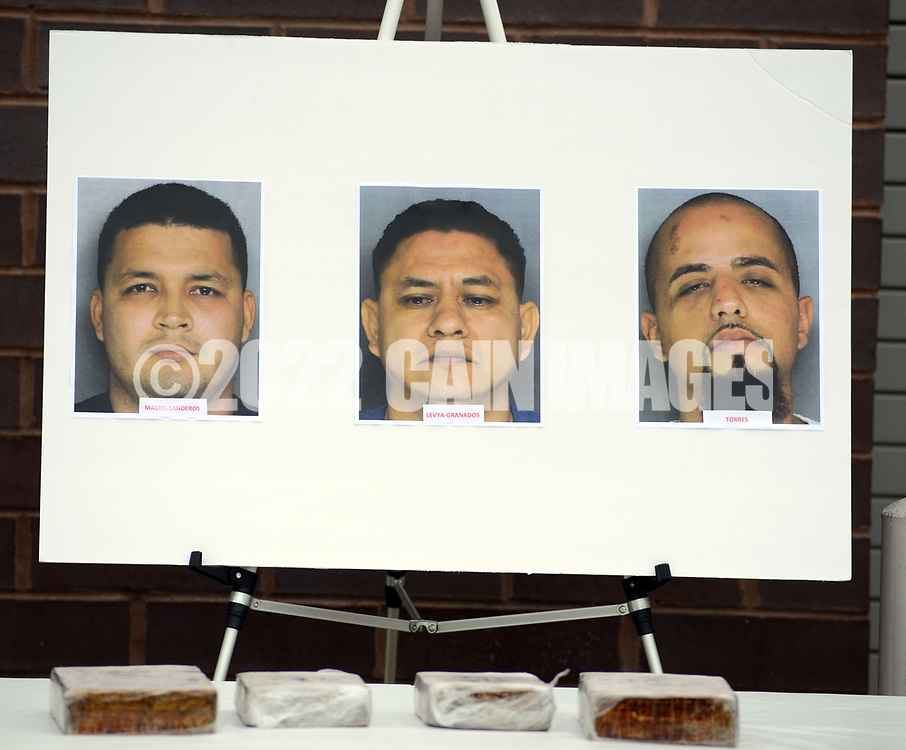 Photos of the suspects on display, and including Edward Torres (right) are seen with the drugs in the foreground, as Police announce a major drug bust involving 6 kilograms of heroin valued at 4 million dollars Thursday, October 05, 2017 at Bensalem Police Department in Bensalem, Pennsylvania.(WILLIAM THOMAS CAIN / For The Philadelphia Inquirer)