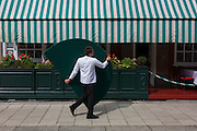 A waiter carries a semi-circular half table outside a Mayfair restaurant