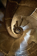 looking down a old circular stone staircase, inside the Sagrada Família church, by Gaudí.