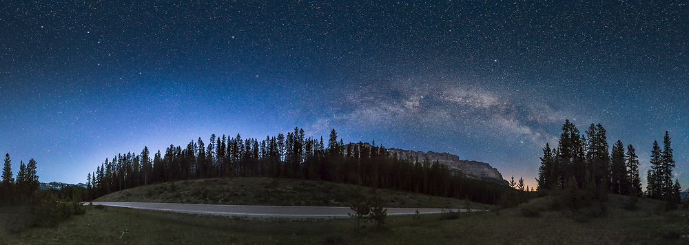 The blue glow of summer solstice twilight in the north (at left below the Big Dipper) and the Milky Way arching over Castle Mountain at right, on the Bow Valley Parkway, in Banff National Park, on a very clear moonless night June 4, 2016. The road seems to lead from the Big Dipper to the Milky Way.<br /> <br /> Despite this being shot after midnight, the sky to the north is still bright with twilight which lasts all night at this latitude near solstice. However, the Milky Way still stands out. In early June the Milky Way arches across the eastern sky and is not yet overhead as it is later in northern summer, making it easier to frame in a pan like this. <br /> <br /> The Big Dipper at upper left is distorted by the map projection used to create the pan, which stretches the sky across the top near the zenith to fill the rectangular frame, like Greenland being distorted in Mercator maps. Polaris is left of top centre - the Dipper bowl still points to it. <br /> <br /> This is a panorama stitched and cropped from 28 panels in 4 tiers of 7 panels each, shot with the iPano motorized panning unit. Each exposure was 20 seconds at f/2.5 with the Sigma 24mm Art lens and Nikon D750 at ISO 5000. Stitched with PTGui.