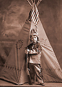 Boy in Indian outfit with a toy gun and a teepee with an American flag on it. CDV circa 1895.