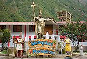 """""""Bienvenidos a Machupicchu"""" (Welcome to Machu Picchu) sign and Inca statue; Machu Picchu Pueblo, Peru."""