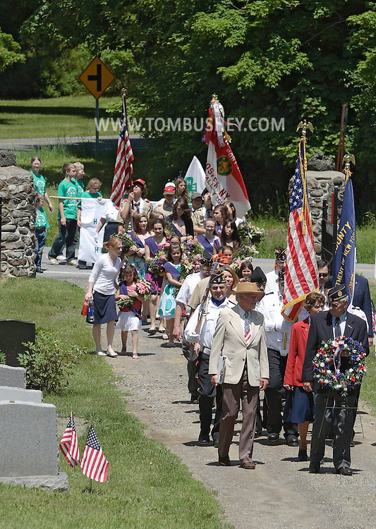 A veteran and American Legion member carries a wreath as he leads a parade through Hamptonburgh Cemetery during Memorial Day ceremonies at Hamptonburgh Cemetery on May 25, 2009. This was the 142nd year flowers have been placed at veterans' graves at the cemetery.