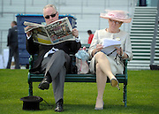 © Licensed to London News Pictures. 19/06/2012. Ascot, UK  A man and woman sit on a bench. Day one at Royal Ascot 19 June 2012. Royal Ascot has established itself as a national institution and the centrepiece of the British social calendar as well as being a stage for the best racehorses in the world.. Photo credit : Stephen Simpson/LNP