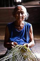Old Iban woman weaving a basket at Murat Longhouse, Skrang River, Sarawak, Borneo, Malaysia.