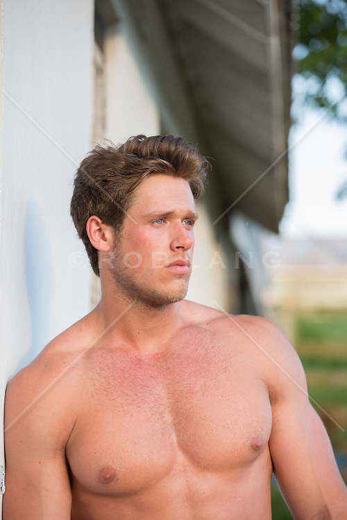 sexy shirtless man leaning against a barn