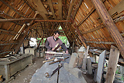 Carpenter at work in a carpentry workshop at the Chateau de Guedelon, a castle built since 1997 using only medieval materials and processes, photographed in 2017, in Treigny, Yonne, Burgundy, France. The Guedelon project was begun in 1997 by Michel Guyot, owner of the nearby Chateau de Saint-Fargeau, with architect Jacques Moulin. It is an educational and scientific project with the aim of understanding medieval building techniques and the chateau should be completed in the 2020s. Picture by Manuel Cohen