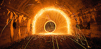 Long Exposure in a tunnel of molten steel wool being spun rapidly around.